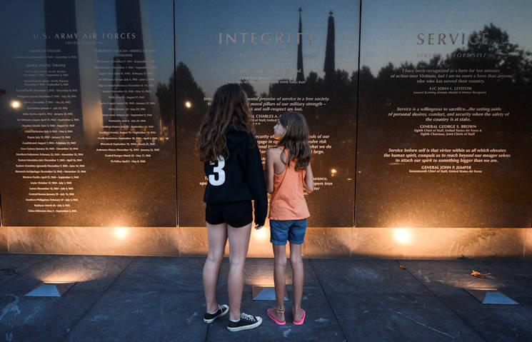 Bridgette Alpar (left), 14, and her 10-year-old sister Meredith, read an engraved wall at the Air Force Memorial in Arlington, Va., Aug. 14, 2015. The Air Force Band played music from the World War II era after a wreath-laying ceremony and a flyover to commemorate the 70th anniversary of the end of World War II. Bridgette and Meredith's father, Maj. David Alpar, is a member of the band. (U.S. Air Force photo by Tech. Sgt. Joshua DeMotts)