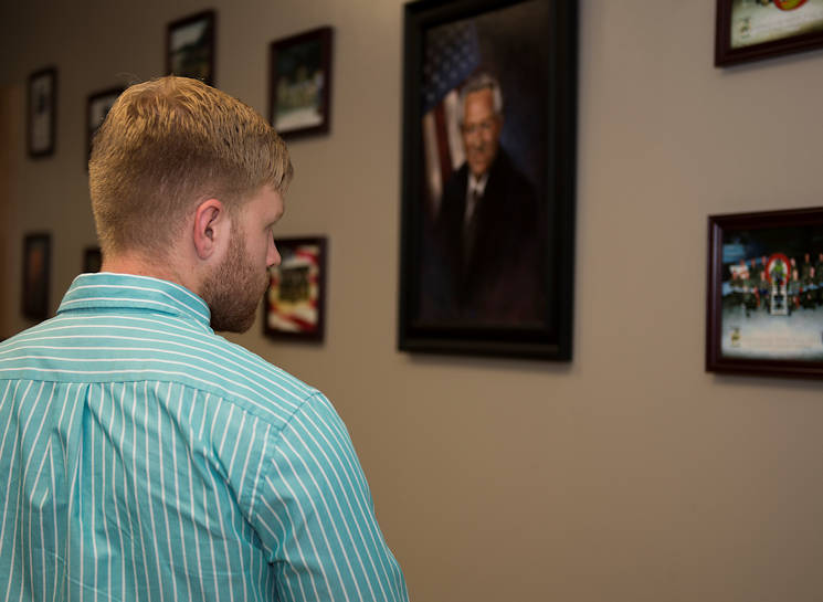 "Colton Whitt, grandson of Kent ""Doc"" Salvage, looks at the photos of his grandfather after a room dedication ceremony to honor his service and sacrifice to the 363rd Training Squadron at Sheppard Air Force Base, Texas, July 14, 2015. Salvage passed away due to a heart attack and is buried in Arlington National Cemetery, Va. (U.S. Air Force photo by Senior Airman Kyle Gese)"
