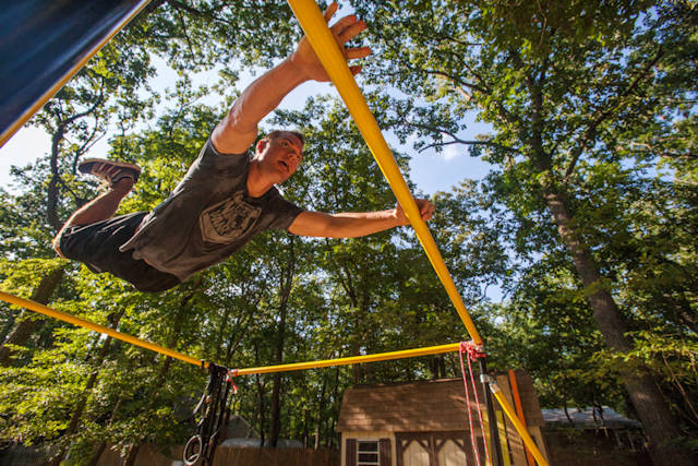 "Tech. Sgt. Justin B. Gielski swings on a set of bars he built in the backyard of his home in Medford, N.J., as he trains to compete on the TV show ""American Ninja Warrior"" Aug. 21, 2015. Gielski placed fifth in the all-military city final on the TV show and advanced to the finals in Las Vegas. Gielski is a loadmaster with the 150th Special Operations Squadron, 108th Wing, New Jersey Air National Guard, located at Joint Base McGuire-Dix-Lakehurst, N.J. (U.S. Air National Guard photo by Master Sgt. Mark C. Olsen)"
