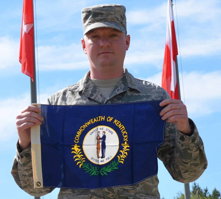 enior Airman Steven Adkins, a broadcast journalist assigned to American Forces Network, Spangdahlem, Air Base, Germany, proudly displays his state flag given to him by his grandfather Don Adkins June 7, 2015, during an assignment for Saber Strike 15 in the Drawsko Pomorskie Training Area in Poland. Saber Strike is a long-standing U.S. Army Europe-led cooperative training exercise. This year's exercise objectives facilitate cooperation amongst the U.S., Estonia, Latvia, Lithuania, and Poland to improve joint operational capability in a range of missions as well as preparing the participating nations and units to support multinational contingency operations. (U.S. Army photo by Sgt. Brandon Anderson, 13th Public Affairs Detachment)