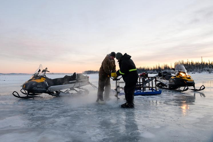 U.S. Air Force Senior Airman Tyler Dray, a range maintenance structures journeyman and Senior Airman Jerry Mitchell, a heavy equipment operator, both assigned to the 354th Civil Engineer Squadron, use an ice auger while constructing a ice bridge in Fairbanks, Alaska, Nov. 20, 2014. The bridge must be constructed every other year to provide access to the $20 million range complex used to train pilots from around the world during Red Flag-Alaska exercises. (U.S. Air Force photo by Staff Sgt. Shawn Nickel)