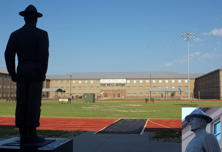 "The morning sun peaks over the rooftop of the Drill Sergeant Academy hitting the black letters from across the way, ""This We'll Defend"". The drill sergeant statue overlooks the physical fitness field at Fort Jackson, Aug. 12, 2015. The statue is dedicated to the founding of the Army's first Drill Sergeant School and the first class of Army Drill Sergeants. (Image created by USA Patriotism! from U.S. Army photos by Satomi Mack-Martin)"