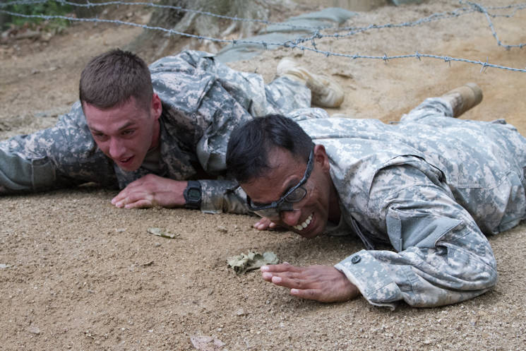 Sgt. Scott Lackey (left), an emergency care non-commissioned officer for the 602nd Aviation Support Battalion, 2nd Combat Aviation Brigade, 2nd Infantry Division and Sgt. Balamurali Devarajan (right), a flight medic with the Company C, 3rd General Support Aviation Battalion, 2nd Combat Aviation Brigade ... use teamwork to crawl under low barbed wire during the 2nd Infantry Division Best Medic Competition on June 23, 2015 at an obstacle course on Camp Casey in the Republic of Korea. Devarajan and Lackey were part of a two-Soldier team hoping for a chance to compete in the 8th U.S. Army Best Medic Competition. The event included day and night land navigation, a written test, and obstacle course, a physical fitness challenge and a buddy run. (U.S. Army photo by Sgt. Jesse Smith)
