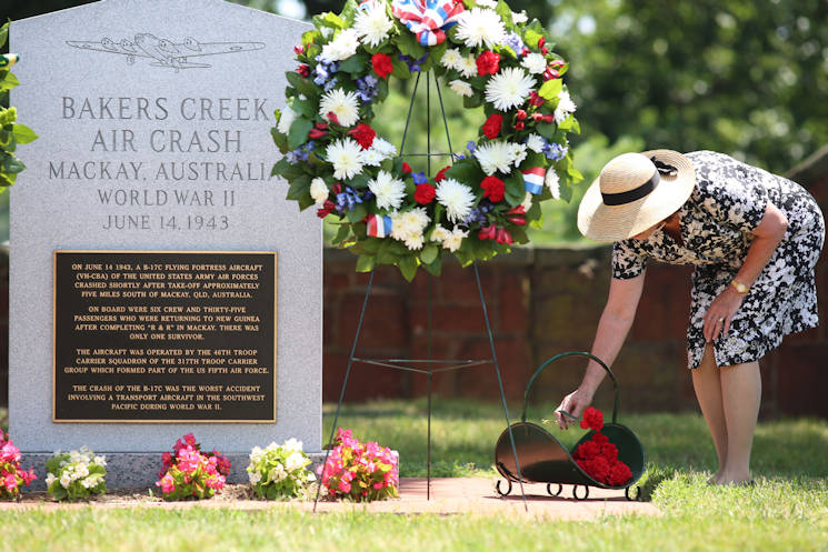 Joan R. Asboth places a flower of remembrance June 12 at Bakers Creek Air Crash Monument near the Selfridge Gate entrance to Arlington National Cemetery on Joint Base Myer-Henderson Hall during the Bakers Creek Memorial Ceremony commemorating the 72nd anniversary of the air crash in Queensland, Australia, that took the lives of 40 Army Air Corps members during World War II. (Joint Base Myer-Henderson Hall PAO photo by Damien Salas)