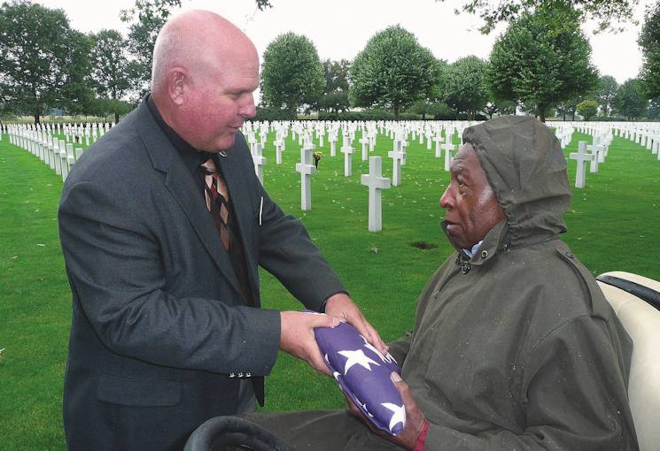 September 13, 2009 - Netherlands American Cemetery Superintendent Mike Yasenchak presents the American flag to veteran Jefferson Wiggins for his role in helping to bury thousands of American service members there during World War II. The flag had been flown over the cemetery in his honor. (Courtesy Photo)