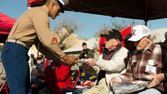 Private Miguel Ramirez, a Marine awaiting training to become a field artillery cannonier, presents a piece of cake to a veteran of Iwo Jima during a ceremony performed by the Marines of the Marine Artillery Detachment at Fort Sill, Okla., Feb. 12, 2015. The Marine Artillery Detachment performed a ceremony to honor the veterans and provided a barbecue meal afterward. (U.S. Marine Corps photo by Sgt. Melissa Karnath)