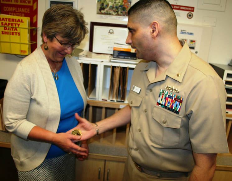 July 13, 2015 - A priceless thank you for job well done... Lt. Cmdr. Carmelo Ayala presents a personal coin to Patricia Koether for her commitment and contribution in Naval Hospital Bremerton's Internal Medicine Department. Ayala has been an avid collector of coin during his naval career of over 28 years and has amassed approximately 3,000 coins. He also has designed his own coin and routinely presents them to staff as well as beneficiaries for their dedication and devotion. (U.S. Navy photo by Douglas H Stutz, NHB Public Affairs)