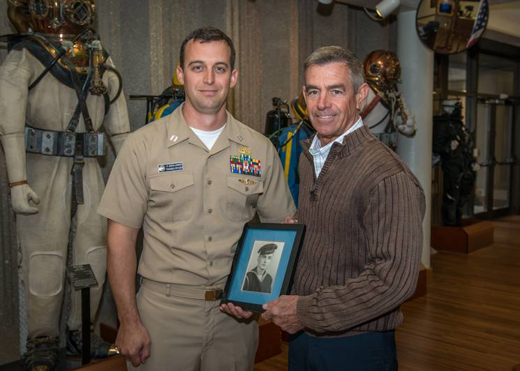February 25, 2015 - Naval Diving Salvage Training Center Training Officer Lt. Jason Junker, U.S. Navy, stands with his father, Dave Junker, and a photo of his great-grandfather who was a U.S. Navy submariner. Dave, who is a retired Navy diver and master chief machinist's mate, is the Naval Surface Warfare Center Panama City Division's Explosive Ordnance Disposal in-service engineering agent and now serves his former community of dive community from the Department of Defense's acquisition community. (U.S. Navy photo by Ron Newsome, NSWC PCD)