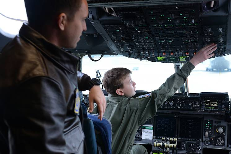 Carver Faull (right) explores the buttons in the cockpit of a C-17 Globemaster III with 1st Lt. Brit Reuscher, 4th Airlift Squadron C-17 pilot, at Joint Base Lewis-McChord, Wash., Feb. 20, 2015. Carver spent the day with members of McChord Field as part of the Pilot for a Day Program. (U.S. Air Force photo by Staff Sgt. Timothy Chacon)