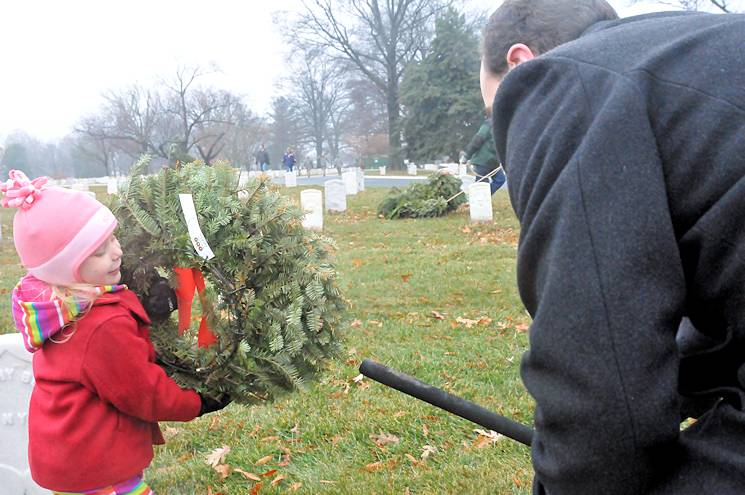 Abby Fries, age 4, helps her father, Theran, clear remembrance wreaths from Arlington National Cemetery on Jan. 22, 2015. Volunteer service can help build and enhance careers for service members transitioning out of the service, according to Joint Base Myer-Henderson Hall's volunteer coordinators. (JBM-HH PAO photo by Jim Dresbach)