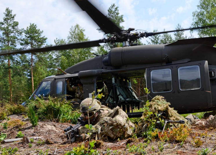 U.S. Soldiers assigned to P Troop, 4th Squadron, 2nd Cavalry Regiment and Polish soldiers assigned to the Polish army's 6th Airborne Brigade pull security after exiting a UH-60L Black Hawk helicopter from Company B, 4th Battalion, 3rd Aviation Regiment (Assault Helicopter Battalion) during an air assault operation July 17, 2015 near Nowa Dęba, Poland. During the training, the U.S. and Polish soldiers were responsible for establishing an observation point and assaulting an objective. The U.S. and Polish troops are part of Operation Atlantic Resolve, an ongoing multinational partnership focused on joint training and security cooperation with U.S. Army allies. (U.S. Army photo by Sgt. Brandon Anderson, 13th Public Affairs Detachment.)