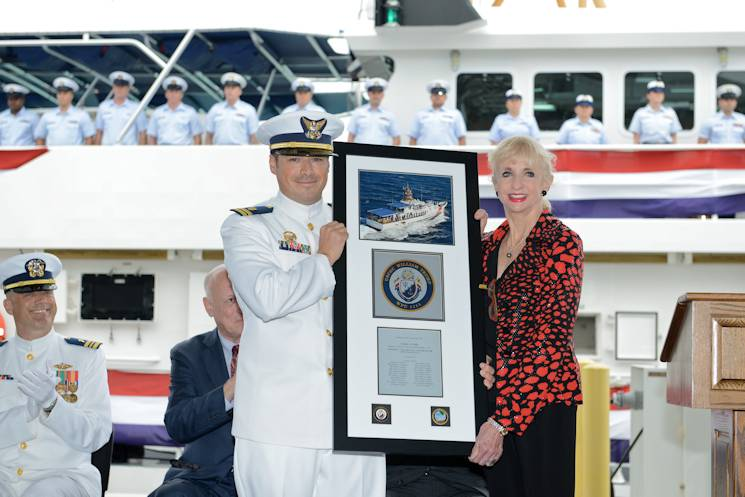 Collette Eddy, daughter of William Trump, presents Lt. Jared Harlow a plaque during the commissioning ceremony for the Coast Guard Cutter William Trump at Coast Guard Sector Key West, Fla., Jan. 24, 2015. Coast Guard hero, Petty Officer 1st Class William Trump, was awarded the Silver Star for valor in action during the assault phase of the landing at Normandy during World War II, more than 70 years ago. (U.S. Coast Guard photo by Petty Officer 3rd Class Jon-Paul Rios)