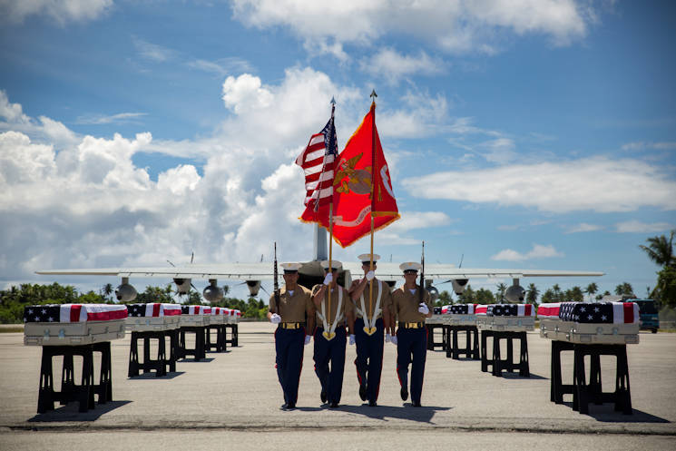A 3rd Marine Regiment color guard takes its place, July 25, 2015, during a repatriation ceremony in Tarawa, Kiribati. The ceremony honored the remains of approximately 36 Marines who fought and died during the Battle of Tarawa during World War II, and were loaded onto a C-130J Hercules aircraft to be transported back home to the United States. (U.S. Marine Corps photo by Cpl. Matthew Bragg)