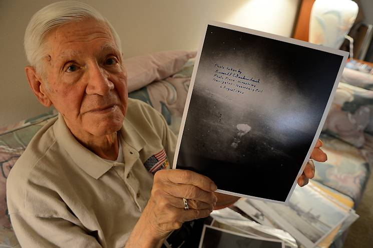 Russell Gackenbach, the navigator aboard the B-29 Superfortress, Necessary Evil, during the nuclear bombing mission over Hiroshima, Japan, on Aug. 6, 1945, shows a photo he took during the historic day, Clearwater, Fla., Feb 10, 2015. Gackenbach is the last surviving member from the mission. (U.S. Air Force photo by Tech. Sgt. Brandon Shapiro)