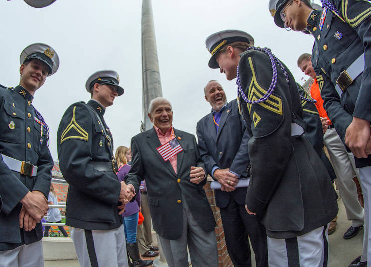 November 21, 2015 - WWII veteran and Bataan Death March survivor U.S. Army Col. Ben Skardon (retired) shares a laugh with members of Clemson University's Reserve Officer Training Corps honor guard, the Pershing Rifles, and David Stalnaker after the dedication ceremony for a plaque at the base of the Memorial Stadium flag pole that honors Skardon for his service and sacrifice. (U.S. Army photo by Staff Sgt. Ken Scar)