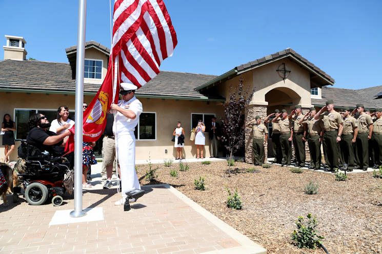 August 21, 2015 - Marines from 1st Explosive Ordnance Disposal Company, 1st Marine Logistics Group look on as retired Staff Sgt. Jason Ross raises the national and Marine Corps colors in front of a new home dedicated to him and his family by The Gary Sinise Foundation. Ross was injured by an improvised explosive device in Afghanistan in 2011 while serving as an explosive ordnance disposal technician and lost both of his legs as a result. The new home has smart technology that will significantly reduce the difficulty of everyday tasks for Ross and allow him and his family to live more comfortably. (U.S. Marine Corps photo by Cpl. Carson Gramley)