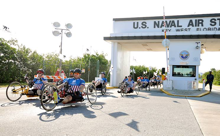 Wounded warriors ride outside the gate of Naval Air Station Key West in the annual Soldier Ride. Wounded Warrior Project's Soldier Ride is an opportunity for wounded service members and veterans to use cycling and the bonds of service in overcoming physical, mental, or emotional wounds. (U.S. Navy photo by Mass Communication Specialist 1st Class Brian Morales)