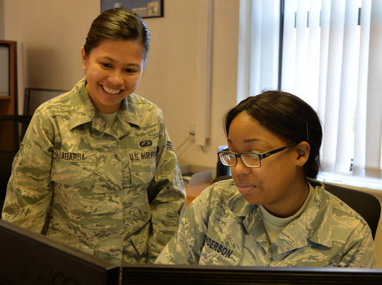 Oct. 5, 2016 - U.S. Air Force Senior Airman Regine Labarda, left, 100th Comptroller Squadron relocation technician, and U.S. Air Force Staff Sgt. Michelle Anderson, 100th CPTS relocations supervisor, discuss an upcoming meeting on RAF Mildenhall, England. Labarda helps new military members in-process and file their travel vouchers. (U.S. Air Force photo by Gina Randall)