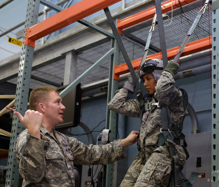 Staff Sgt. Dustin Jespersen, 28th Operations Support Squadron Survival, Evasion, Resistance, and Escape specialist, left, instructs Chief Master Sgt. Sonia Lee, 28th Bomb Wing command chief, on emergency parachute training at the SERE building at Ellsworth Air Force Base, S.D., Feb. 10, 2016. Ejection is a last resort for aircrew members who are trained to stay calm while ejecting and avoid tensing up when landing. (U.S. Air Force photo by Airman Donald Knechtel)