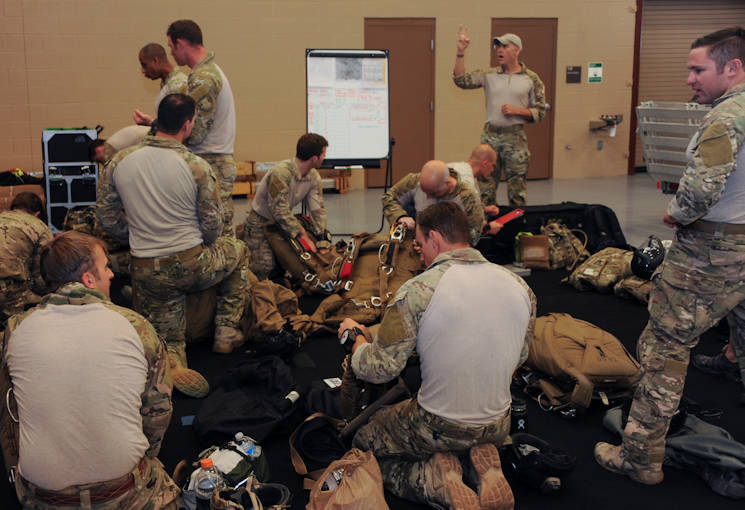Master Sgt. David Biddinger, 563rd Rescue Group jumpmaster course instructor speaks to U.S. Airmen as they prepare equipment during the Military Freefall Jumpmaster Course at Davis-Monthan Air Force Base, Ariz., June 28, 2016. Students vary from tactical air control party specialists, combat controllers, pararescuemen, and survival, evasion, resistance and escape specialists from all different commands. (U.S. Air Force photo by Airman Nathan H. Barbour)