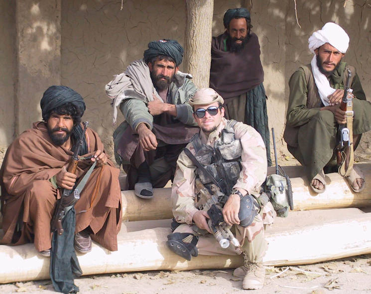 Now-Chief Warrant Officer 2 Brad Fowers with Afghan fighters and warlords, who opposed the Taliban (2001). Fowers served on one of the first Special Forces detachments from the U.S. Army Special Operations Command's 5th Special Forces Group (Airborne) to arrive in Afghanistan following 9-11. Their mission was to destroy the Taliban regime and deny Al-Qaida sanctuary in Afghanistan. They scouted bomb targets and teamed with local resistance groups. (Photo courtesy of U.S. Army Chief Warrant Officer 2 Brad Fowers)