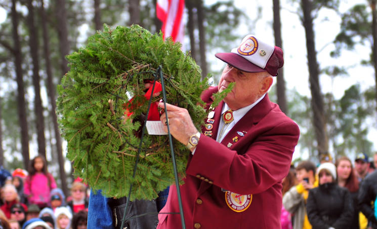"December 17, 2016 - Retired Sgt. Maj. Jacob Roth, formally of the 5th Special Forces Group (Airborne), hangs a holiday wreath representing the service of fallen prisoners of war during a Wreaths Across America event at the Sand Hills State Veteran's Cemetery in Spring Lake, NC. According to Senate Resolution 726 of the 110th U.S. Congress, ""recognizes the sacrifices our veterans, service members and their families have made, and continue to make, for our great Nation."" (U.S. Army photo by Pfc. Hubert D. Delany III)"