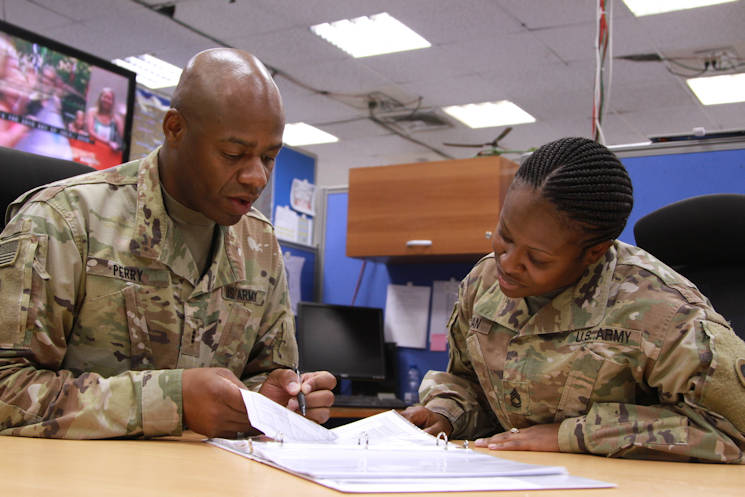 July 26, 2016 - Army Chief Warrant Officer 3 Thomas E. Perry III, mobility officer with the 1st Sustainment Command (Theater), assists Army Sgt. 1st Class Jade V. Morman, sustainment cell noncommissioned officer with the 1st TSC, with her warrant officer packet. (U.S. Army Reserve photo by Sgt. 1st Class Naurys Marte)