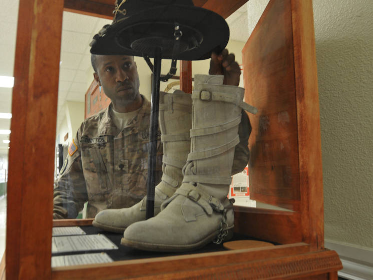 Spc. Tamarkion Britton, a construction equipment repairer with 3rd Cavalry Regiment, arranges the Cav Hat worn by Col. John Richardson, the 74th colonel of the regiment, January 5, 2016 inside 3rd CR's headquarters building at Fort Hood, Texas. Britton built the display case for the items. (Photo by Staff Sgt. Tomora Clark, 3rd Cav. Regt. Public Affairs NCOIC)