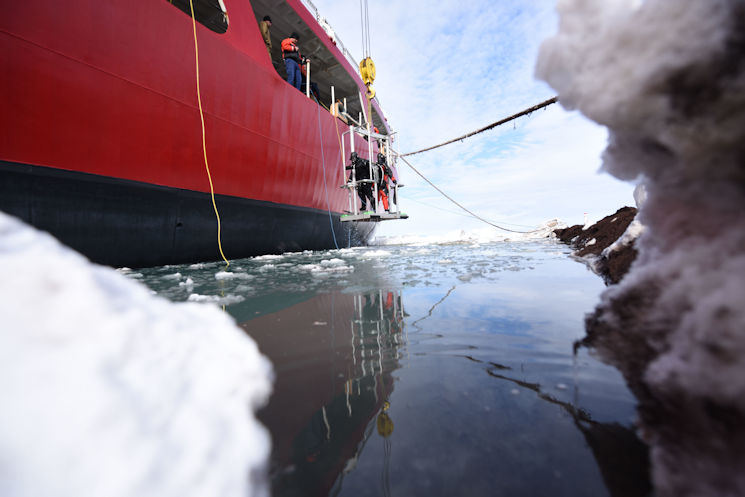 The Coast Guard Cutter Polar Star deck department lowers two Coast Guard divers from the cutter into McMurdo Sound at the National Science Foundation's McMurdo Station, Antarctica, Jan. 19, 2016. (U.S. Coast Guard photo by Petty Officer 2nd Class Grant DeVuyst)