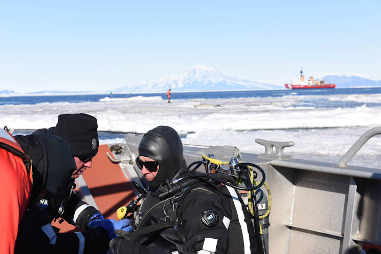 Coast Guard divers check equipment on Petty Officer 2nd Class Dylan Smith, a Coast Guard Regional West diver, on one of the Coast Guard Cutter Polar Star's landing craft in McMurdo Sound, Antarctica, Feb. 6, 2016. As the standby diver, Smith was prepared to enter the water in an emergency situation. (U.S. Coast Guard photo by Petty Officer 2nd Class Grant DeVuyst)