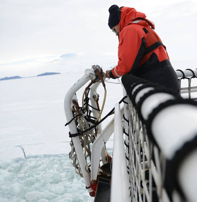 Seaman Morrow Tapia, a boatswain's mate of the watch on the Coast Guard Cutter Polar Star, ties down a safety net on the cutter's flight deck while underway in McMurdo Sound, Antarctica, Jan. 9, 2016. The BMOW makes rounds about the ship to ensure that cargo and equipment is safely stowed while at sea. (U.S. Coast Guard photo by Petty Officer 2nd Class Grant DeVuyst)