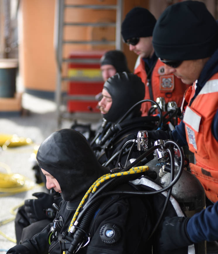 Coast Guard and Navy divers perform an equipment check before a dive from the Coast Guard Cutter Polar Star at the National Science Foundation's McMurdo Station, Antarctica, Jan. 19, 2016. The dive team exercises a series of equipment checks to mitigate risk in the remote austere Antarctic environment. (U.S. Coast Guard photo by Petty Officer 2nd Class Grant DeVuyst)