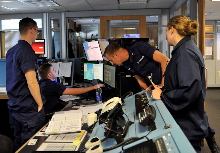 The operations specialists on duty listen intently to a radio call in Coast Guard Sector Southeartern's command center on August 12, 2016. The initial call that came in is the beginning of a search and rescue case involving three people off Great Point in Massachusetts. (U.S. Coast Guard photo by Petty Officer 3rd Class Nicole J. Groll)