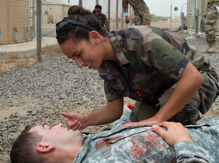 Caporal-chef Adjudant, a French military medical officer, uses hand gestures to communicate with a U.S. servicemember acting as a simulated casualty during a combat lifesaver course practical exam June 23, 2016, at Camp Lemonnier, Djibouti. The French participants brought their own medical supplies to show how they treat patients. (U.S. Air Force photo by Staff Sgt. Eric Summers Jr.)