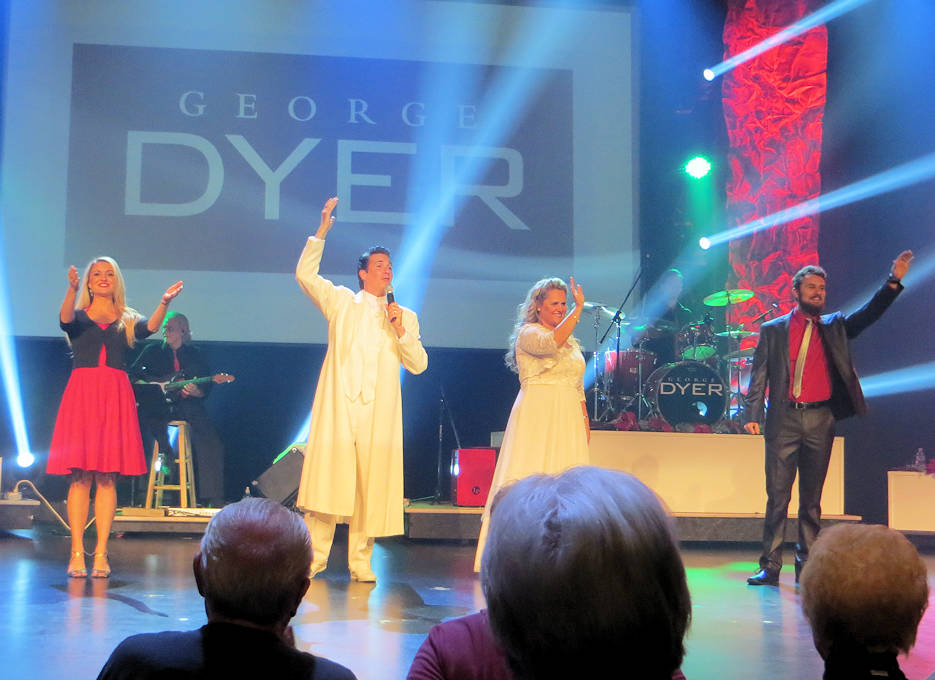 November 12, 2016 - The amazing, versatile singer George Dyer (wearing white coat) with his talented family (L-R -- daughter/Kendra, wife/Clarisse, and son/Garrett ... wave to the audience during a standing ovation after performing an inspiring patriotic song at their must see show at the Mickey Gilley Theatre in Branson, Missouri. (Photo by USA Patriotism!)