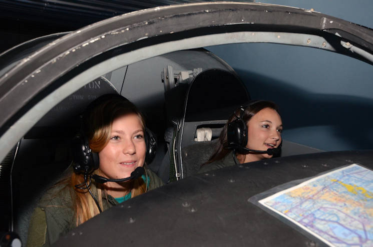 "July 14, 2016 - Two middle school girl students experience flight simulation during a recent visit to the U.S. Air Force's Museum of Aviation in Warner Robins, Georgia. They were among 18 middle school-aged girls attending the Air Force Reserve change of command ceremony, Maj. Gen. Stayce Harris and taking part in the museum's Mission Quest Flight Simulation program. The group attended the museum's program as part of the ""Spectacles 2016"" summer camp hosted by Wesleyan College (U.S. Air Force courtesy photo)"