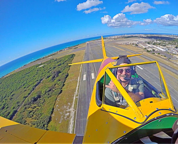 Harry Greene flashes a shaka while flying his Boeing Stearman Kaydet Primary Trainer airplane over Kalaeloa Airport, Oahu, Jan. 31, 2016. Greene is a helicopter pilot at Coast Guard Air Station Barbers Point and an aircraft enthusiast in his off-duty time. (U.S. Coast Guard photo by Petty Officer 2nd Class Tara Molle)