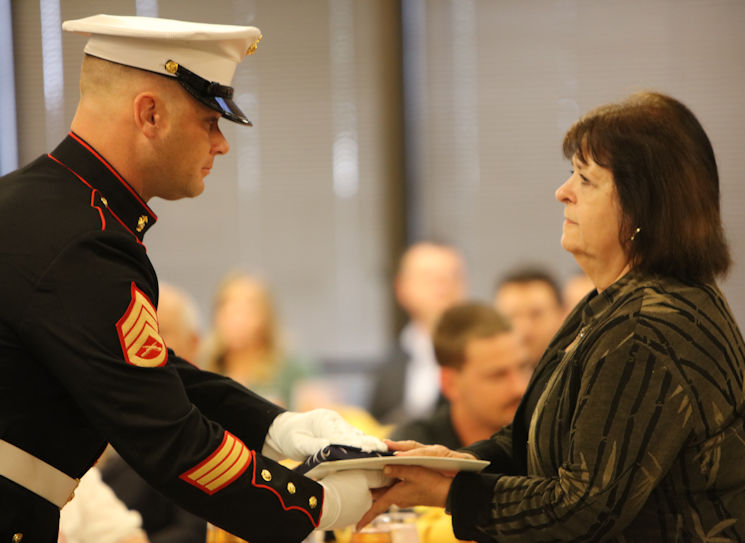 "Marine Corps Staff Sgt. Christian Wolanski, a recruiter at Recruiting Station St. Louis, delivers a flag to a Gold Star mother at the 7th Annual Gold Star Family Luncheon on Oct. 1, 2016 in St. Louis, MO. The term ""Gold Star"" refers to a family who lost a loved one in war. (U.S. Marine Corps photo by Cpl. Jennifer Webster)"
