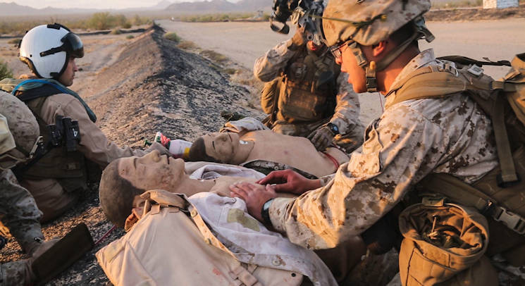 Service members from 1st Marine Division apply first aid to simulated casualties during a Tactical Recovery of Aircraft and Personnel mission in El Centro, Calif., April 28, 2016. The TRAP mission was a part of a Marine Air-Ground Task Force Integration Exercise with units from Marine Aircraft Group 39 as a part of MAG-39's new MAGTF integration effort. (U.S. Marine Corps photo by Cpl. Alissa Schuning)