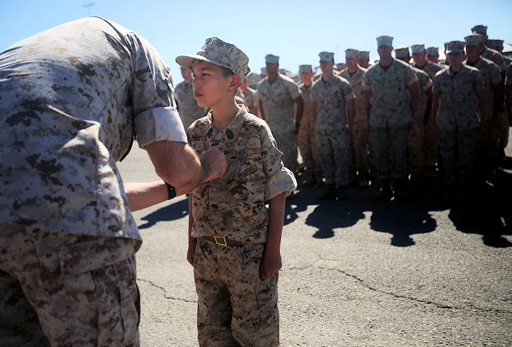Nathan Aldaco, a 12 year-old boy with hypoplastic left heart syndrome, stands at attention as Col. Jaime O. Collazo pins on the Master EOD badge during a Make-A-Wish event supported by 7th Engineer Support Battalion, 1st Marine Logistics Group, aboard Camp Pendleton, Calif., March 24, 2016. Collazo is the 1st MLG chief of staff. Marines with 7th ESB and Explosive Ordnance Disposal helped to make Nathan's wish of becoming a Marine come true by demonstrating the capabilities of their EOD robots and detonating TNT, C4, dynamite and blasting caps, while the heavy equipment operators gave him the opportunity to ride the D7 dozer and the excavator, in which he dug a pit, built a berm, and broke several large tree trunks. (U.S. Marine Corps photo by Sgt. Laura Gauna)