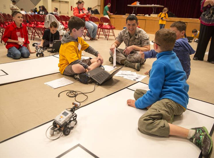 Air Force Capt. Michael K. Kan, center right, a bioenvironmental engineer, talks with robotics club students at the Camp Foster Community Center at Okinawa, Japan, February 20, 2014, during the first robotics competition sponsored by Department of Defense Education Activity Okinawa District. (U.S. Marine Corps photo by Cpl. Joey Holeman)