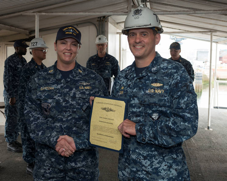 "August 2, 2016 - U.S. Navy Captain Joe Turk, commanding officer of USS Michigan (SSGN 727)(Blue), presents Chief Culinary Specialist Dominique Saavedra with her submarine qualification certificate during a ceremony at Puget Sound Naval Shipyard. Saavedra the first female enlisted Sailor to earn the ""dolphins."" (U.S. Navy photo by Chief Petty Officer Kenneth Takada)"