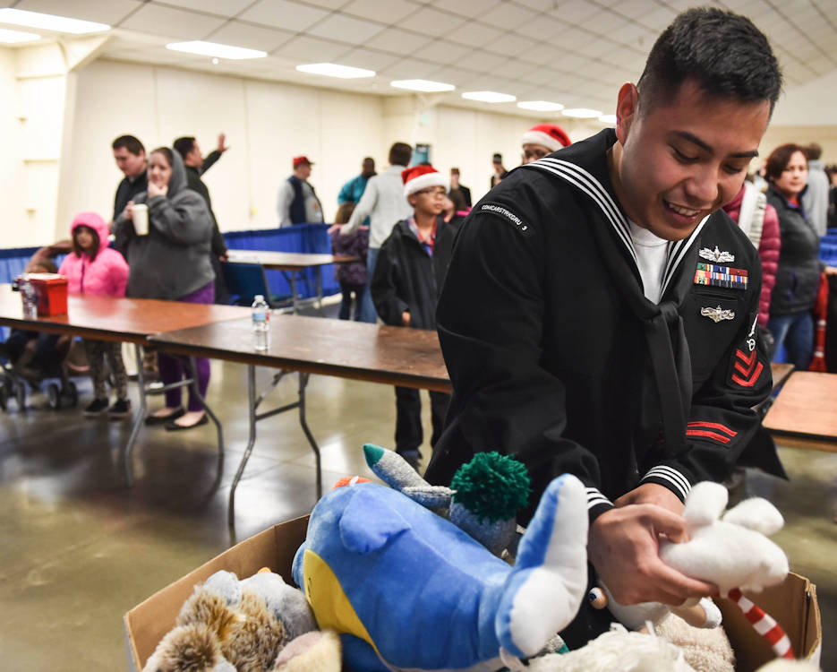 December 17, 2016 -  Petty Officer 1st Class Angelo Espiridion, from Vallejo, Calif., stationed with Commander, Strike Group Three, searches for a specific stuffed animal request for a child during the Toys for Tots-Kitsap distribution event at the Kitsap Fairgrounds. Kitsap Marines, Sailors and volunteers with the organization devoted more than an approximated 1,500 hours to collect and reach more than 2,000 children, who received gifts throughout the 2016 campaign effort in the county, with nearly 1,800 receiving gifts on Saturday alone. (U.S. Navy photo by Mass Communication Specialist 1st Class Cory Asato)