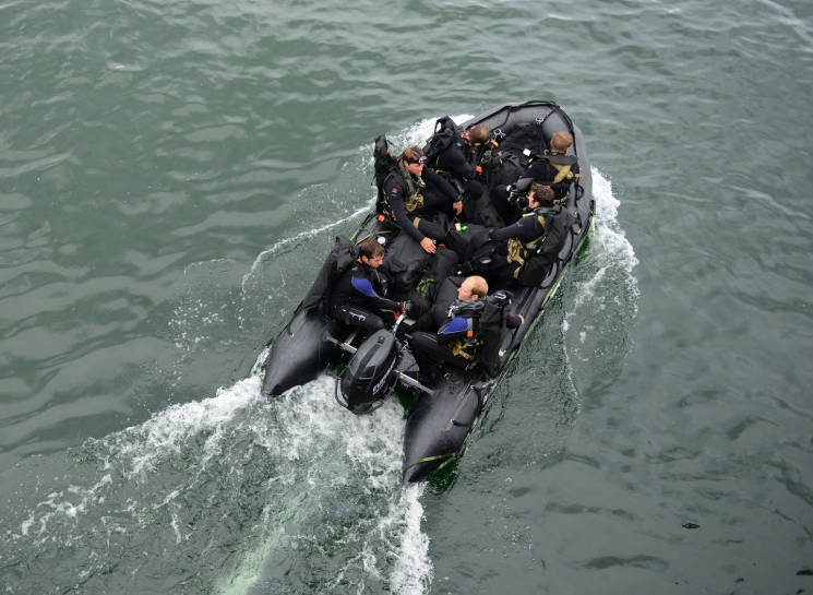 A Zodiac, rigid-hulled inflatable boat, filled with six members of a U.S. Army special forces unit, out of Army Base Fort Carson, Colo., transits away from the Coast Guard Cutter Fir, a 225-foot Sea-going Buoy Tender, after the cutter's crew lowered the Zodiac into the Pacific Ocean near Warrenton, Ore., during a joint-agency operation, June 22, 201 (U.S. Coast Guard photo by Petty Officer 1st Class Levi Read)