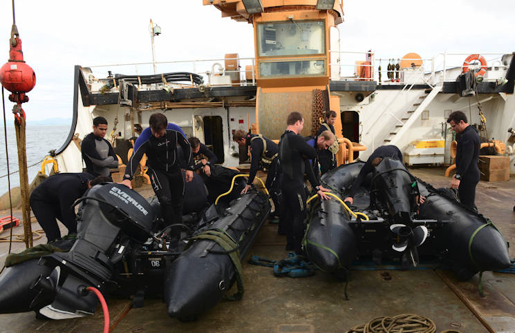 Soldiers from the U.S. Army 10th Special Forces Group, out of Army Base Fort Carson, Colo., prepare their Zodiac rigid-hulled inflatable boats for deployment while aboard the Coast Guard Cutter Fir, a 225-foot Sea-going Buoy Tender during transit off the northern coast of Oregon, June 22, 2016. The cutter supplied equipment storage and deployment during a joint-agency operation. (U.S. Coast Guard photo by Petty Officer 1st Class Levi Read)