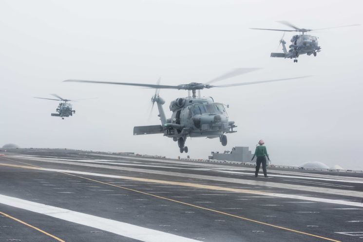 Jan. 20, 2016 - Three MH-60R Sea Hawks assigned to the Raptors of Helicopter Maritime Strike Squadron (HSM) 71 prepare to land on USS John C. Stennis' (CVN 74) flight deck. Providing a combat-ready force to protect and defend collective maritime interests, Stennis as part of the great green fleet is operating in the U.S. 3rd Fleet area of operations on a regularly scheduled Western Pacific deployment. (U.S. Navy photo by Mass Communication Specialist 3rd Class Kenneth Rodriguez Santiago)