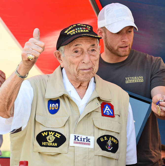 World War II Veteran Irving M. Abramson gives a thumbs-up during a story recounting a kiss he received, from actress Marlene Dietrich, while he recovered from wounds inflicted during the Battle of the Bulge. Abramson received the Purple Heart and other medals for his service during World War II at the Arlington Heights' Memorial Day commemoration, May 30, 2016. (U.S. Army photo by Sgt. Aaron Berogan)
