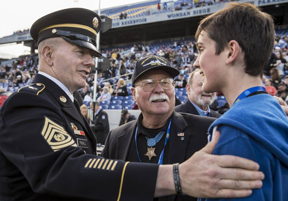 "December 27, 2016 - Army Command Sgt. Maj. John W. Troxell, left, senior enlisted advisor to the Chairman of the Joint Chiefs of Staff, meets Medal of Honor recipient Harvey C. ""Barney"" Barnum Jr. center, a retired Marine Corps officer, and his relative before conducting the coin toss during the 2016 Military Bowl at the Navy-Marine Corps Memorial Stadium in Annapolis, MD. The Wake Forest Demon Deacons defeated the Temple Owls 34-26 during the college bowl, which benefits the USO and other organizations supporting the armed forces and their families. (DoD photo by U.S. Army Sgt. James K. McCann)"