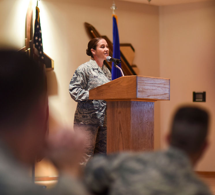 U.S. Air Force Senior Master Sgt. (SMS) Angela Blue, 1st Maintenance Squadron first sergeant, speaks to Paul W. Airey NCO Academy students during their graduation December 20, 2017. During her speech, Blue spoke to graduates about personal development and walking the line as a leader.  SMS Angela Blue is a an Air Force Combat Action Medal and a Purple Heart recipient. (U.S. Air Force photo by Senior Airman Dustin Mullen)