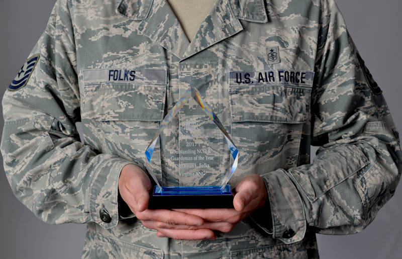 U.S. Air Force Tech. Sgt. Ryan Folks holds his NCO award at Joint Base Langley-Eustis, VA, Dec. 21, 2017. After returning from deployment, Folks was awarded the Air Force achievement award, NCO in charge of the year and overall guardsmen of the year awards. (U.S. Air Force photo by Airman 1st Class Alexandra Singer)